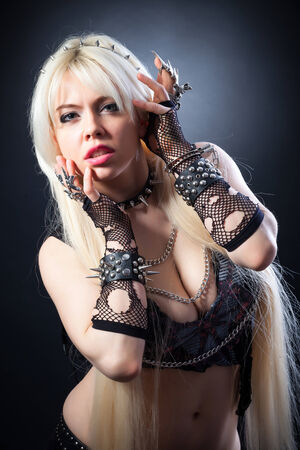 attractive woman with blade metal claw, studio shot on a black background photo
