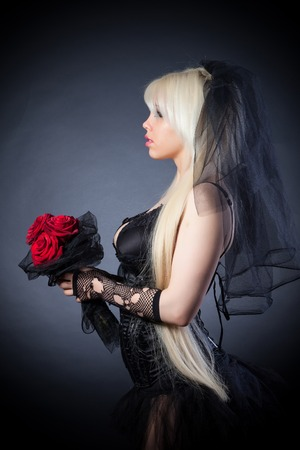 black widow in grief  with flowers  with a veil on a black background photo