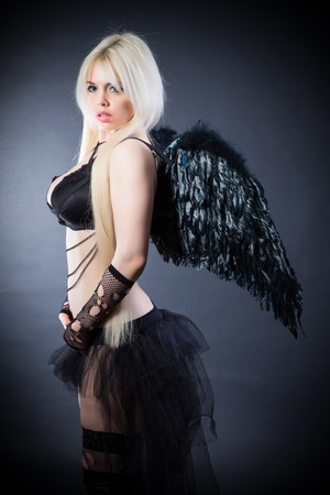 devil girl: Woman in the lingerie with black angel wings against the black background Stock Photo