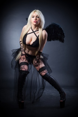angry angel: Woman in the lingerie with black angel wings against the black background Stock Photo