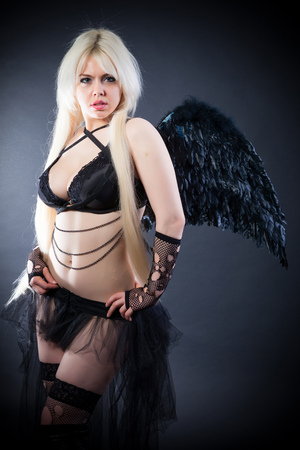 incubus: Woman in the lingerie with black angel wings against the black background Stock Photo