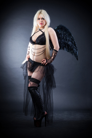succubus: Woman in the lingerie with black angel wings against the black background Stock Photo
