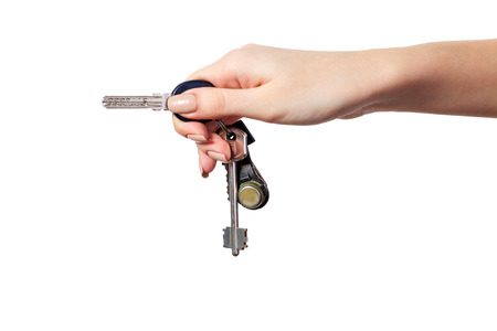 Female hand holding a key to the house, image is taken over a white background. photo