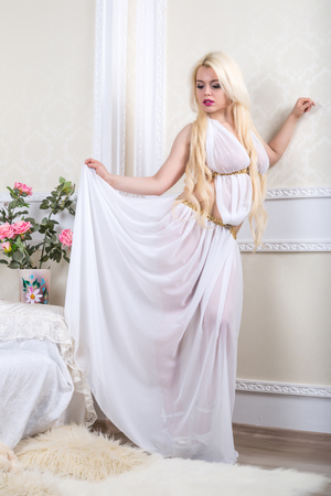 Luxurious blonde woman in a white dress in front of modern classical room photo