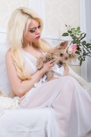 Luxurious blonde woman in a white dress with a dog  pekingese in front of modern classical room photo