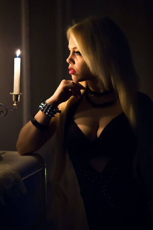 portrait of a beautiful woman with a candle on a black background photo