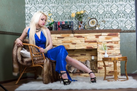 Luxurious blonde woman in a blue dress in front of classical room photo