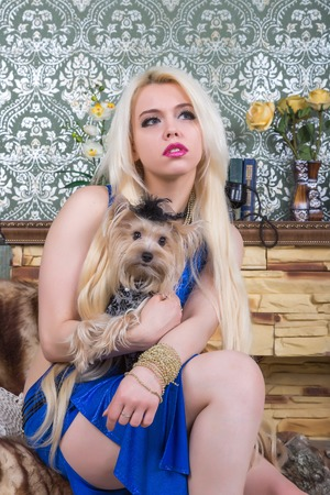 Luxurious blonde woman in a white dress with a dog  pekingese in front of classical room photo