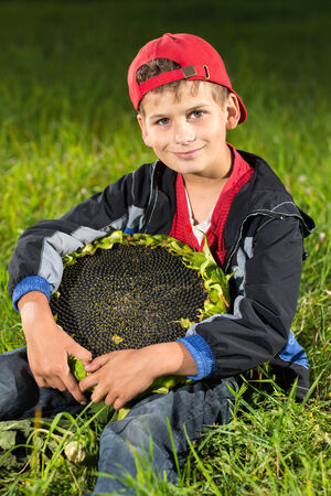 Cute happy boy hold sunflower in a summer garden photo