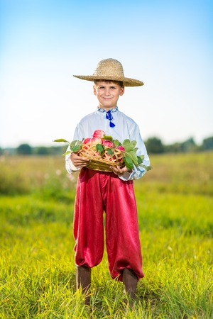 Happy boy hold Organic Apples in Autumn Garden.Healthy Food.Outdoors.Park. Basket of Apples.Harvest concept .Smiling farmer photo
