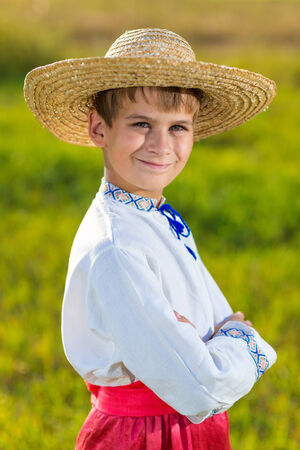 Young boy wearing traditional Ukraine clothes in wheat and poppy field on summer day outdoors background photo
