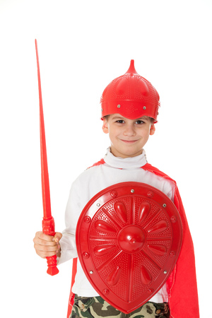 Young Boy Dressed Like a knight holding a sword and shield isolated on white photo