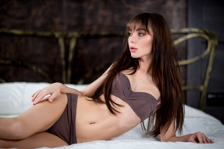 Young brunette sexy glamour woman in white bikini on the bed photo