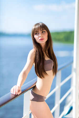 Attractive girl wearing white sexy swimwear  enjoying warm sunny day on the yacht deck, luxury lifestyle, holidays and vacation concept photo