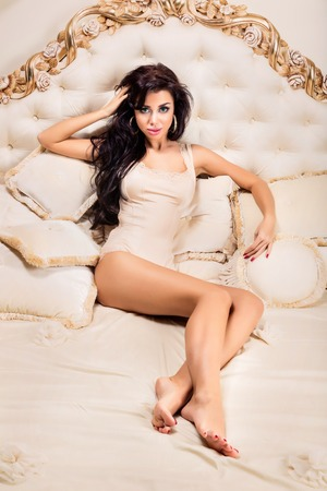 Beautiful and attractive young adult female brunette sensuality woman posing on bed in exclusive apartment photo
