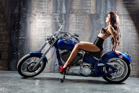 Attractive girl on a motorbike  in a studio photo