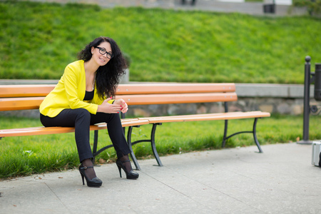 A beautiful girl is sitting on a park bench on a background of green nature photo