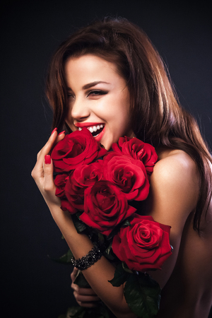 Stylish beautiful young woman holding red roses bouquet, tender flowers in hands, brunette female over dark background photo
