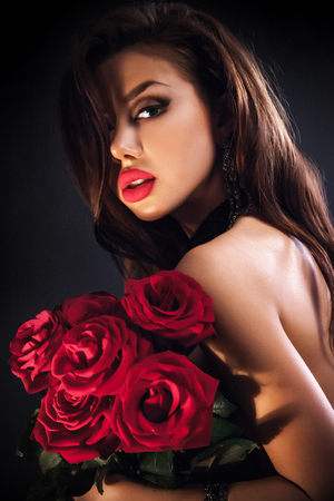 Stylish beautiful young woman holding red roses bouquet, tender flowers in hands, brunette female over dark background Stock Photo - 26896609