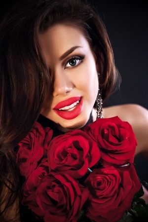 Stylish beautiful young woman holding red roses bouquet, tender flowers in hands, brunette female over dark background Stock Photo - 26896611