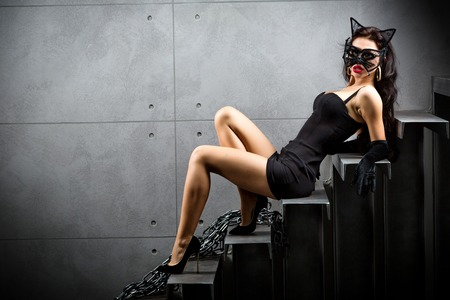 mujer desnuda sentada: mujer sexy en traje de catwoman miente en las escaleras en el patio del edificio Foto de archivo