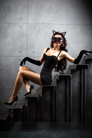 sexy woman in catwoman suit lying on stairs at backyard of building photo