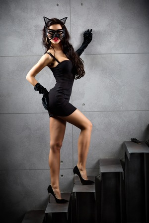 sexy woman in catwoman suit staying on stairs at backyard of building photo