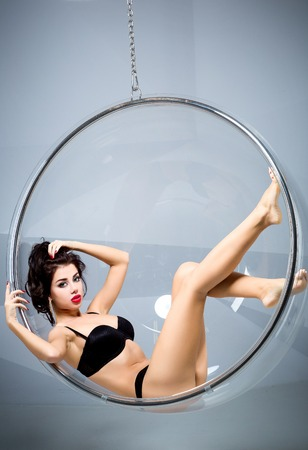 Sexy woman sitting in a chair suspended round photo