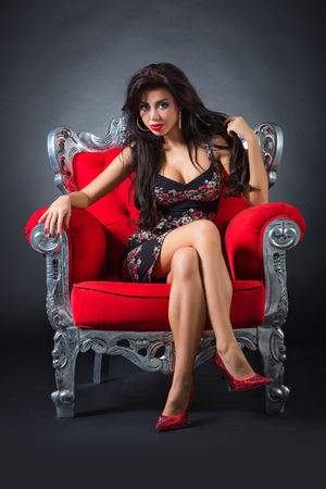 Young woman in a red chair. Retro style. photo