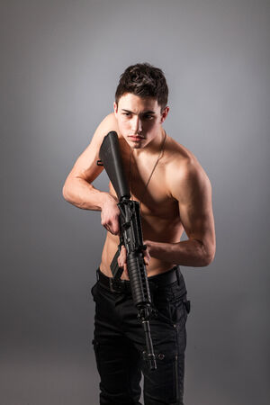 Handsome bare-chested soldier is holding a rifle on black background photo