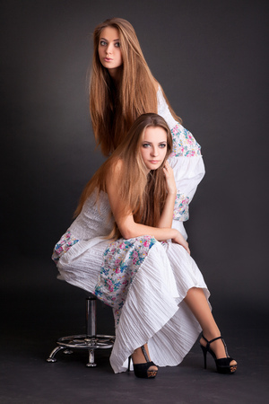 Two beautiful girls twins, isolated on the black background photo