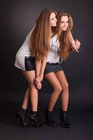 Two beautiful girls twins on the black background photo