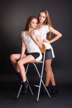 Two beautiful girls twins, on the black background photo