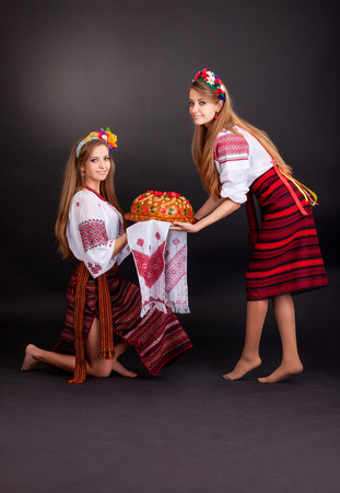 Young women in ukrainian clothes, with garland and round loaf on black background photo