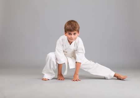 karate boy: Karate boy in white kimono fighting isolated on gray background