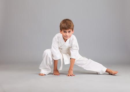 Karate chlapec v bílém kimonu bojích izolovaných na šedém pozadí Reklamní fotografie