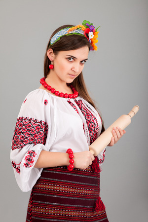 dominion: Housewife with rolling pin. Woman wears Ukrainian national dress isolated on grey background Stock Photo