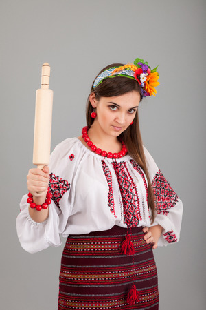 Housewife with rolling pin. Woman wears Ukrainian national dress isolated on grey background photo