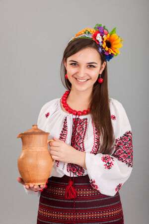 Attractive woman wears Ukrainian national dress is holding a jug isolated on a grey background photo