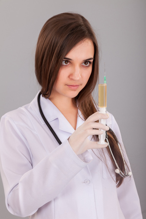 Woman doctor holding a filled syringe in hand on grey background photo
