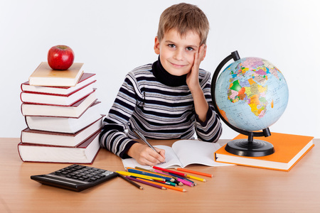child studying: Cute schoolboy is writting isolated on a white background Stock Photo