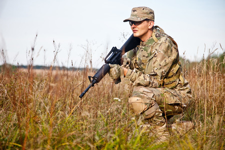 police helmet: Soldier with a rifle in the field