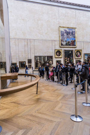 PARIS - AUGUST 4: Visitors take photo of Leonardo DaVincis Mona Lisa at the Louvre Museum, August 4, 2013 in Paris, France. The painting is one of the worlds most famous.