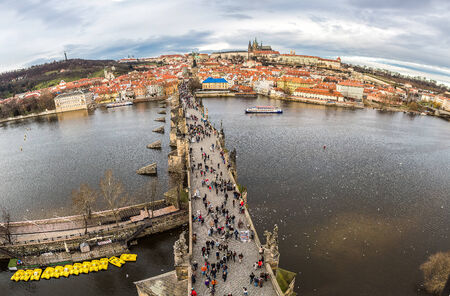 december 21: PRAGUE, CZECH REPUBLIC - DECEMBER 21: Tourists on Charles Bridge, December 21, 2013, Prague,Czech Republic. Annually Prague is visited by more than 3,5 million tourists
