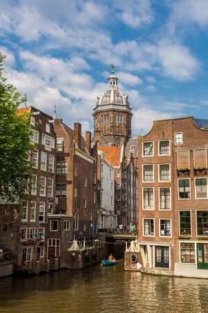 populous: AMSTERDAM, NETHERLANDS - AUGUST 19: Canal and St. Nicolas Church in Amsterdam. Amsterdam is the capital and most populous city of the Netherlands on August 19, 2014