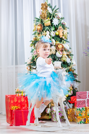 beautiful girl next to a horse rocking near a Christmas tree photo