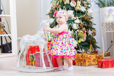baby girl next to a horse rocking near a Christmas tree photo