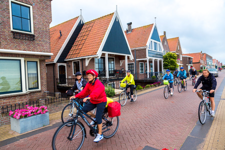 volendam: VOLENDAM, NETHERLANDS - AUGUST 20: Traditional houses and bicyclists in Holland town Volendam, Netherlands on August 20, 2014