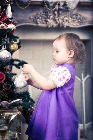 Cute little baby girl is  decorating the christmas tree photo