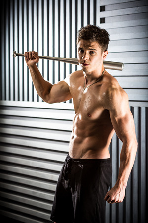 Close-up portrait of muscular man posing with a bat photo